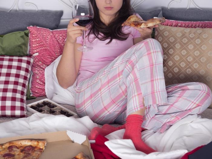 ベッドの上でピザを食べる女性