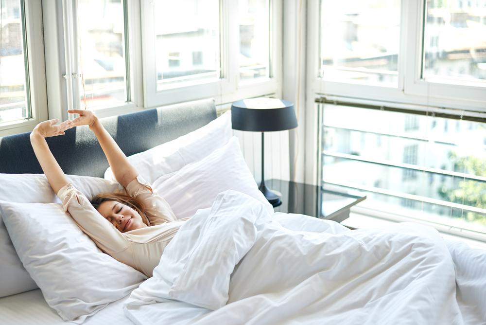 ベッドで起き抜けにのびをする女性