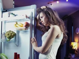 夜中に冷蔵庫を見ている女性