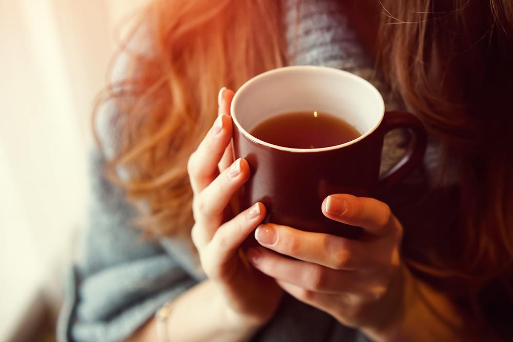 温かいお茶を飲む女性の手元