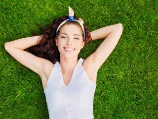 芝生で寝ている笑顔の女性