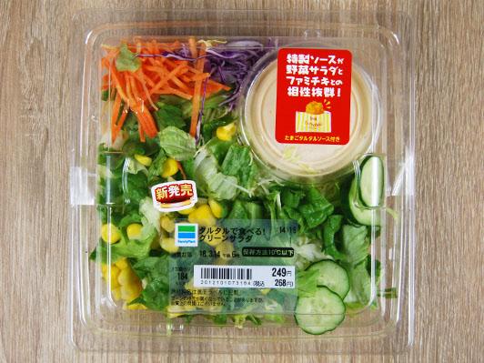 未開封のプラスチックの容器にグリーンサラダとコーン、人参、ソースが入っている
