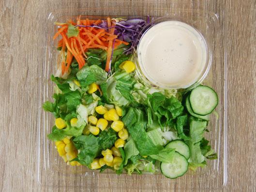 開封後のプラスチックの容器にグリーンサラダとコーン、人参、ソースが入っている
