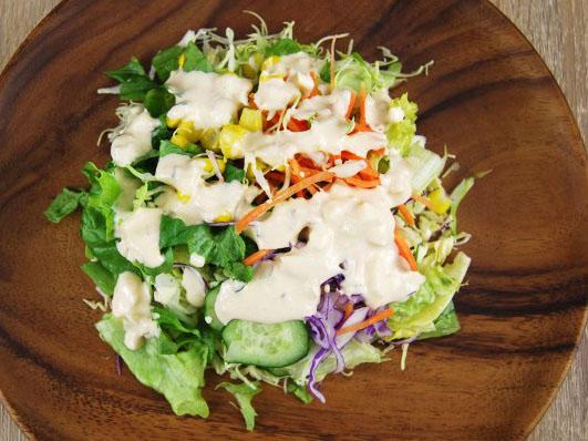 木皿の上にグリーンサラダとコーン、人参が盛り付けられ、ソースがかけてある