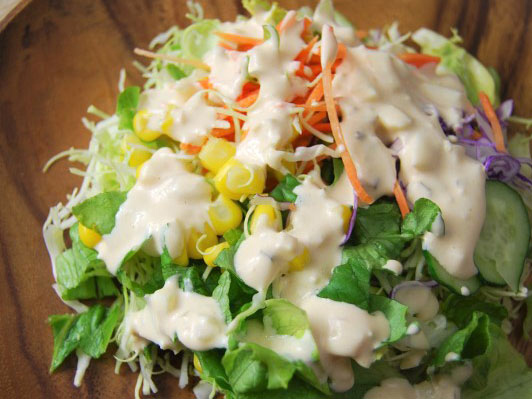 木皿の上にグリーンサラダとコーン、ソースがかかっている