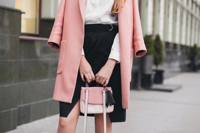 ピンクコートとバックを持つ女性