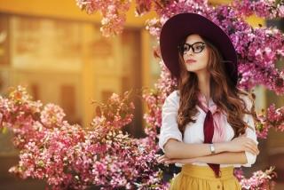 ピンクの桜、梅の花の前にメガネをかけた凛とした女性が立っている
