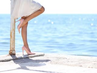 美脚の女性が海辺に立っている