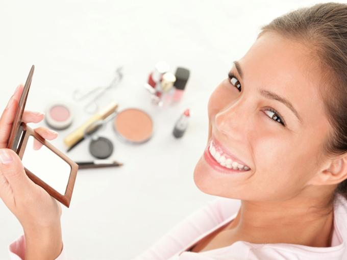 メイク中に鏡を見て笑顔の女性