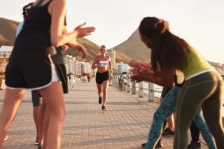走っている女性と応援している人々