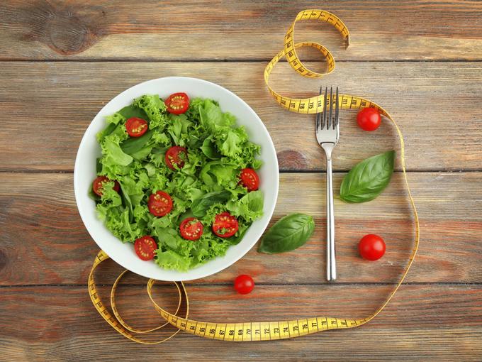 テーブルの上にサラダの入ったお皿と、ダイエットを意識したメジャー