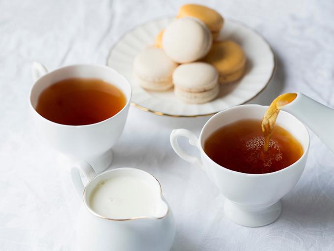 白いテーブルの上に紅茶の入ったカップ2つにマカロン