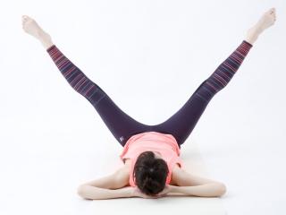 寝転んだ女性が脚を左右に大きく広げてエクササイズ