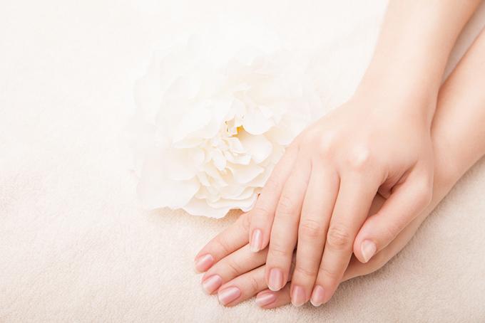 女性の手が重なっている画像