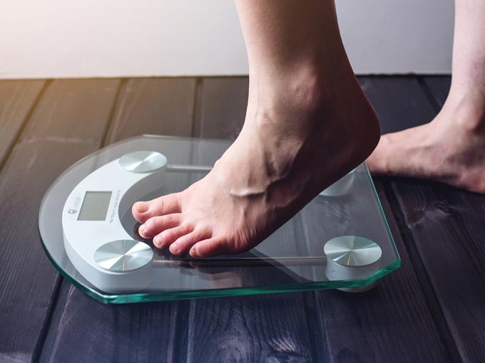 体重計に乗ろうとする女性
