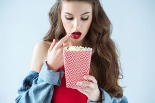 赤い口紅を受けた女性がポップコーンを持っている
