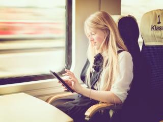 女性が電車内でスマホを操作している画像