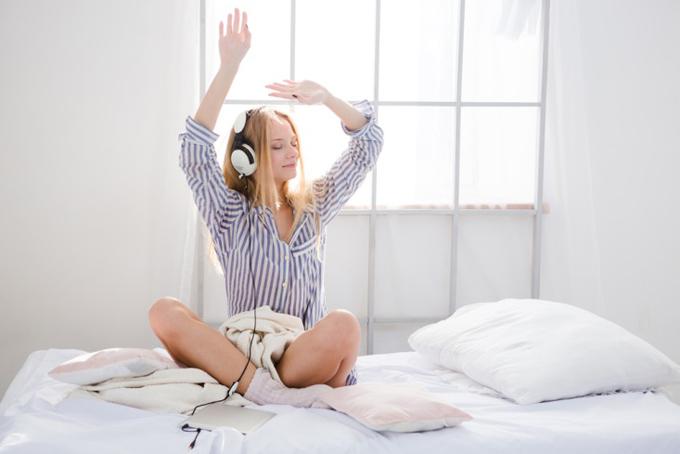 ストライプのシャツを着た女性がベッドの上で音楽を聴いている