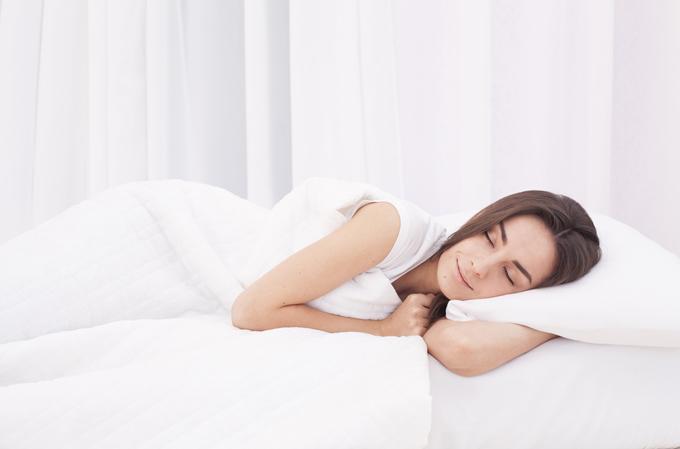 ベッドで寝が入りを打つ女性