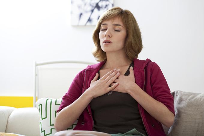 女性が胸に両手を当てて呼吸を意識している