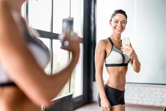 鏡に自分の姿を映す女性