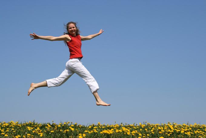 パンツスタイルでジャンプする女性