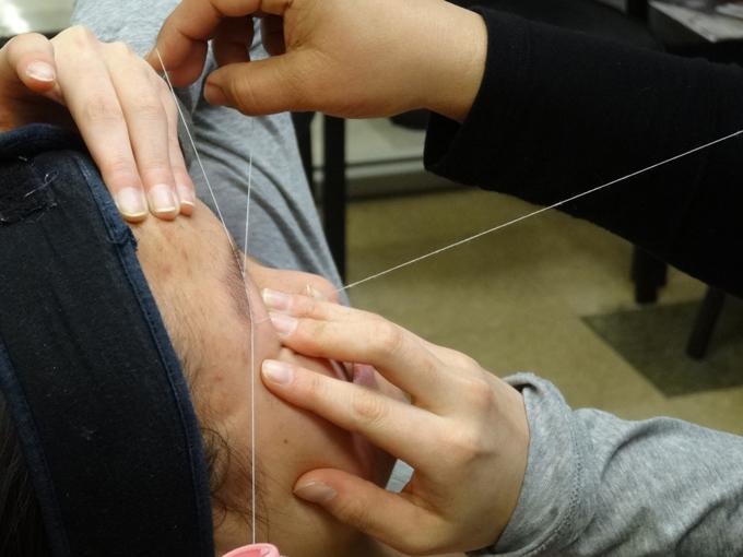 糸で眉毛をお手入れされている女性