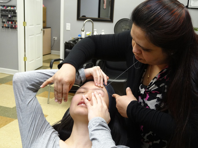 糸で眉毛をお手入れされて痛そうな女性