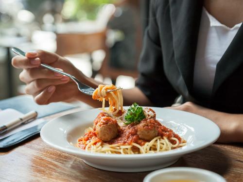 外食でパスタを食べる女性