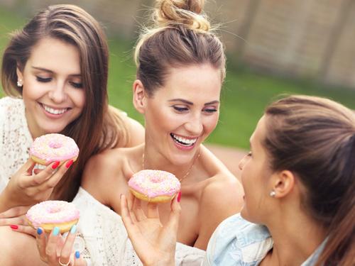 笑顔で甘いドーナツを食べる女性たち