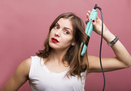 ヘアアイロンを使う女性