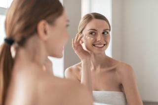女性が鏡を見ながら肌にクリームをに塗っている