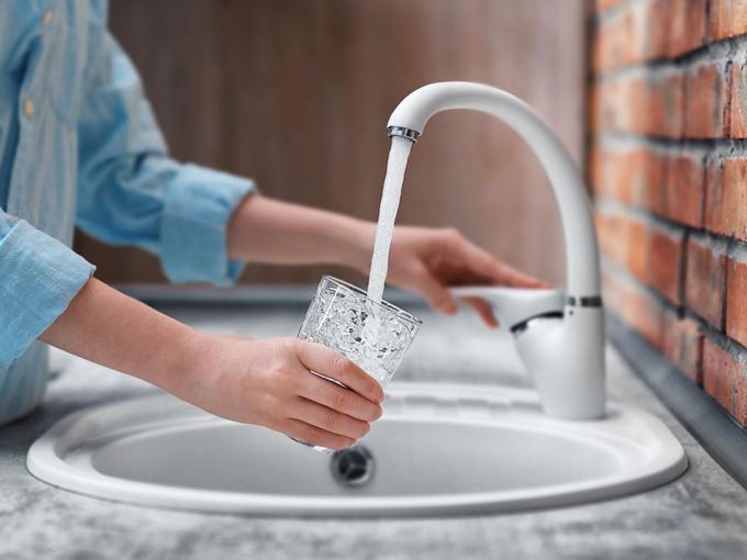 水道水をコップに入れる女性