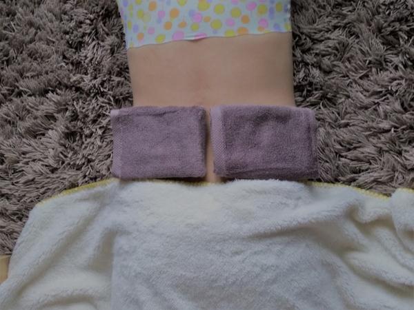 腎臓の位置にこんにゃく湿布をする女性