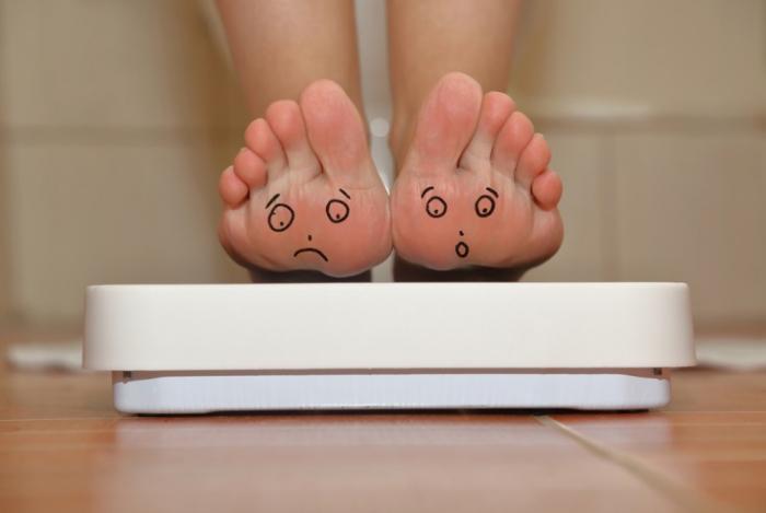 体重計におそるおそる乗る女性。
