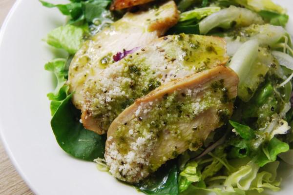 お皿の上に葉物野菜とチキン、パスタにバジルソースがかかったアップの写真
