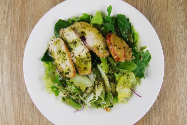 お皿の上に葉物野菜とチキンにバジルソースがかけてある