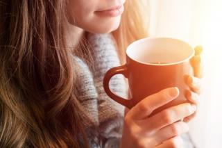 カップを手にお茶を飲もうとしている女性