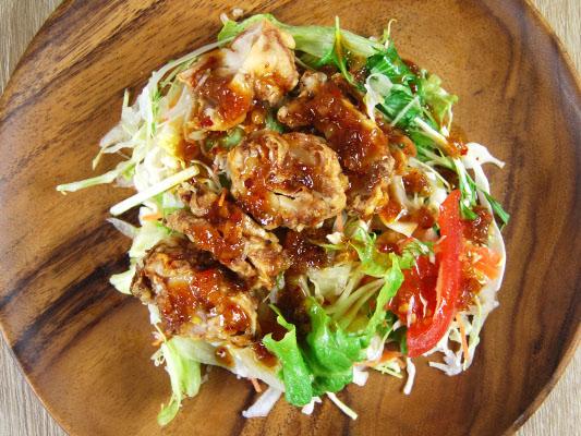 開封後の木皿に盛った、香味だれのソースと油淋鶏、サラダ