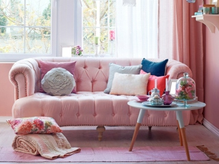 日当たりの良い窓際にピンクのソファにジュータンなどインテリアが素敵