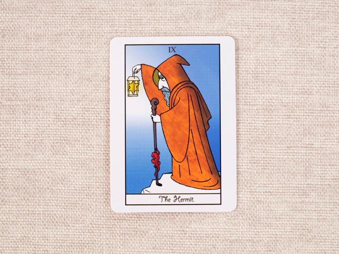 ランプと杖を手に、フードを被った老人の絵柄のカード