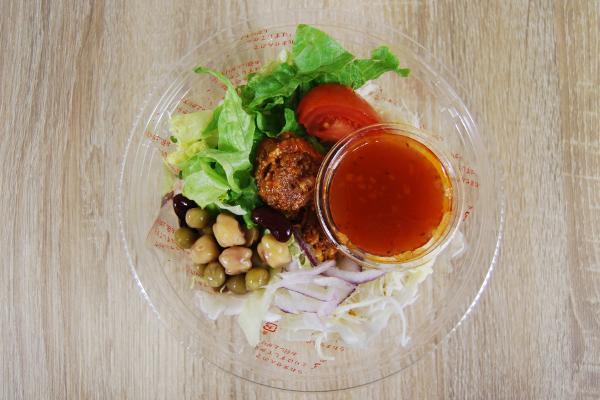 プラスチック容器開封後のタコスミートとトルティーヤチップのサラダ