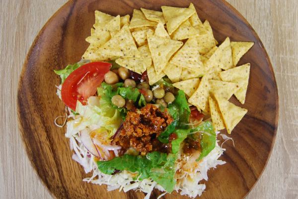 木皿の上に盛り付けたタコスミートとトルティーヤチップのサラダ
