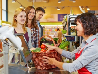スーパーのレジに並ぶ女性