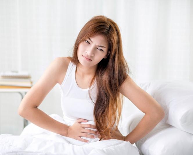 ベッドの上でお腹を押さえる女性の画像