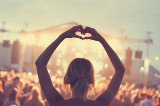 ライブ会場で手を高く上げ、ハートをつくる女性