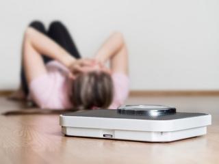 ダイエットに失敗して落ち込む女性と体重計