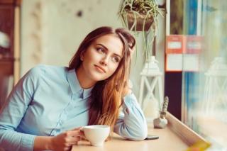 窓辺でお茶を飲みながら外を見ている女性