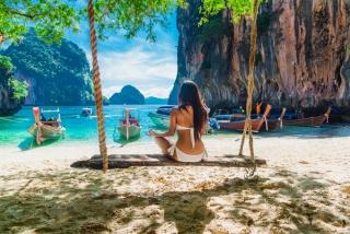 南国ビーチの前のブランコに座っている水着姿の女性