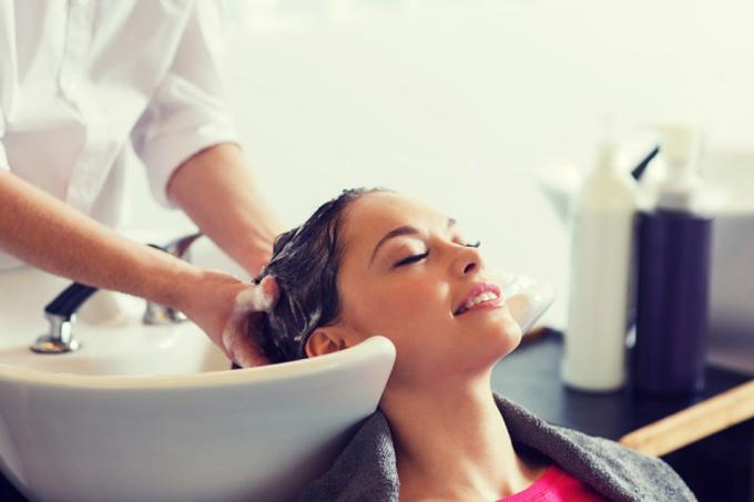 シャンプー台で髪を洗ってもらう女性